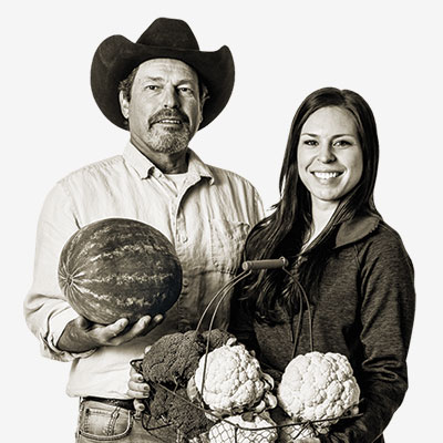 a man in a cowboy hat holding a watermelon standing next to a woman holding a basket of vegetables