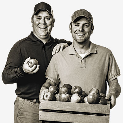 two men standing next to each other while one holds a crate of apples