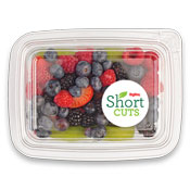 raspberries, blueberries, blackberries and sliced kiwi in a plastic container