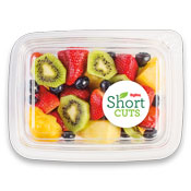 kiwi, strawberries, blueberries, and pineapple in a plastic container