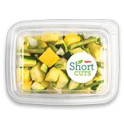 sliced zucchini, summer squash, white onions, and asparagus in a plastic container