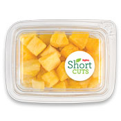 top down view of a plastic container full of pineapple chunks