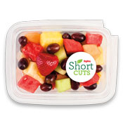 strawberries, red grapes, watermelon, pineapple, honeydew, and cantaloupe in a plastic container