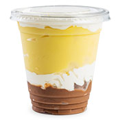 A cup of mostly vanilla pudding with a layer of whipped topping diving the vanilla and chocolate