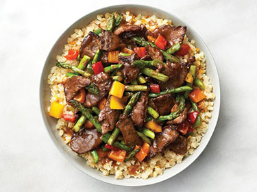 a top down view of a bowl of beef and asparagus stir-fry
