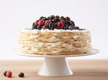 Berry crepe cake on a cake stand with berries on top
