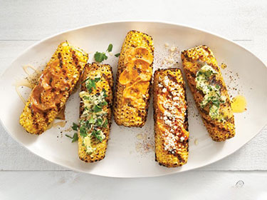 five ears of charred sweet corn on a white platter