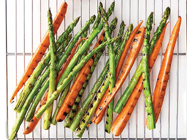 grilled asparagus and carrots sitting on a cooling rack