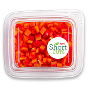 Top down view of a plastic container filled with diced up red peppers